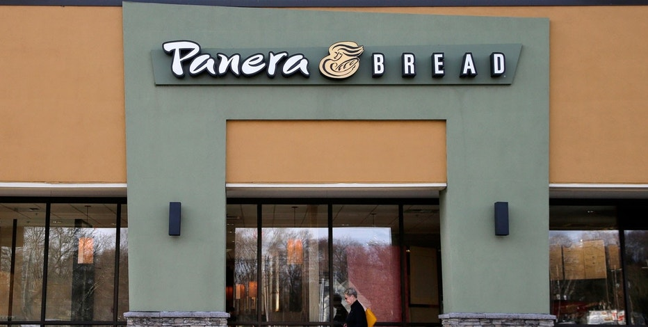 In this Wednesday, April 12, 2017, file photo, a passer-by walks near an entrance to a Panera Bread restaurant in Natick, Mass. In a deal announced Wednesday, Nov. 8, 2017, Panera Bread says it is buying bakery chain Au Bon Pain to boost its presence in airports, hospitals and colleges.