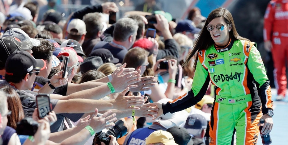 In this Feb. 22, 2015, file photo, driver Danica Patrick greets fans as she is introduced before the start of the Daytona 500 NASCAR Sprint Cup series auto race at Daytona International Speedway in Daytona Beach, Fla. Patrick announced plans Friday, Nov. 17, 2017, to run just 2 races in 2018, the Daytona 500 and the Indianapolis 500, and end her full-time driving career.