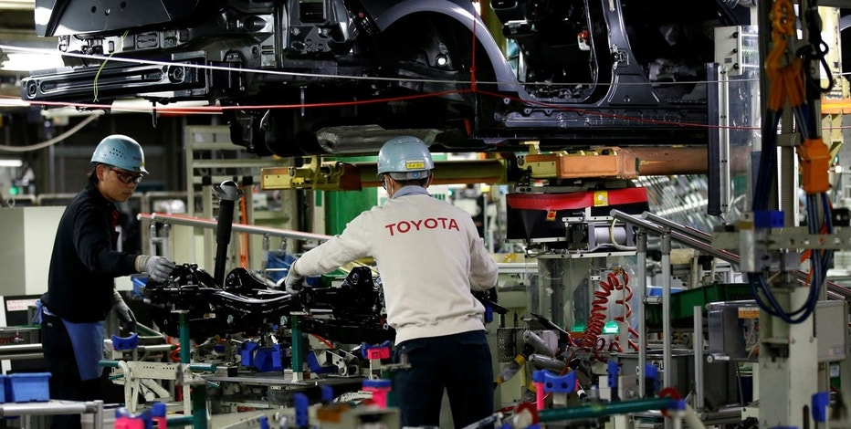 Employees work on an assembly line of the Toyota Motor Corp's Prius hybrid car at the Tsutsumi plant in Toyota central Japan