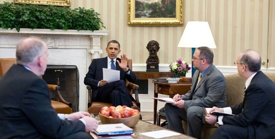 U.S. President Barack Obama (C) receives a briefing on the earthquake in Japan and the tsunami warnings across the Pacific in the Oval Office, March 11, 2011.