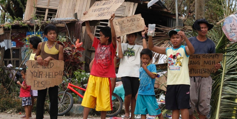 Children hold signs asking for help and food along the highway, after Typhoon Haiyan hit Tabogon town in Cebu Province, central Philippines November 11, 2013