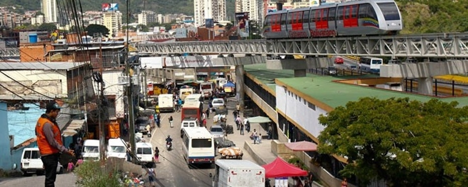 Commuters travel near the slum district of Petare in Caracas in August 2013.
