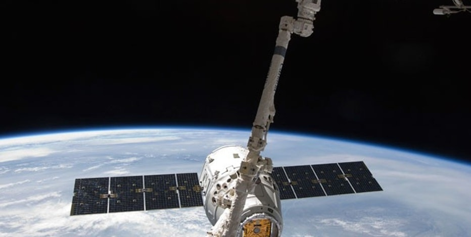 With the Earth in the background, the SpaceX Dragon commercial cargo craft is seen as it is grappled by the International Space Station's Canadarm2 robotic arm.