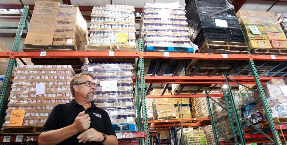 FILE- In this Monday, July 30, 2012 file photo, Dave Krepco, director of the Second Harvest Food Bank, checks on inventory at the food bank warehouse in Orlando, Fla. The Commerce Department reports on wholesale stockpiles and sales in July. The report will be issued Wednesday Sept. 10, 2014. (AP Photo/John Raoux, File)