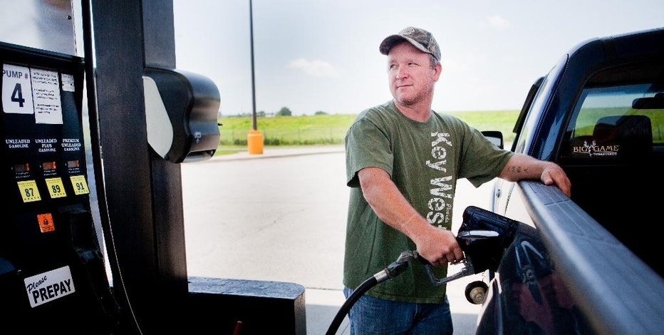 FILE - In this July 1, 2014 file photo, Lance Thompson pumps gas into his truck at a Love's station in St. Joseph, Mo. The Labor Department reports on U.S. consumer prices in August on Wednesday, Sept. 17, 2014. (AP Photo/St. Joseph News-Press, Sait Serkan Gurbuz, File)
