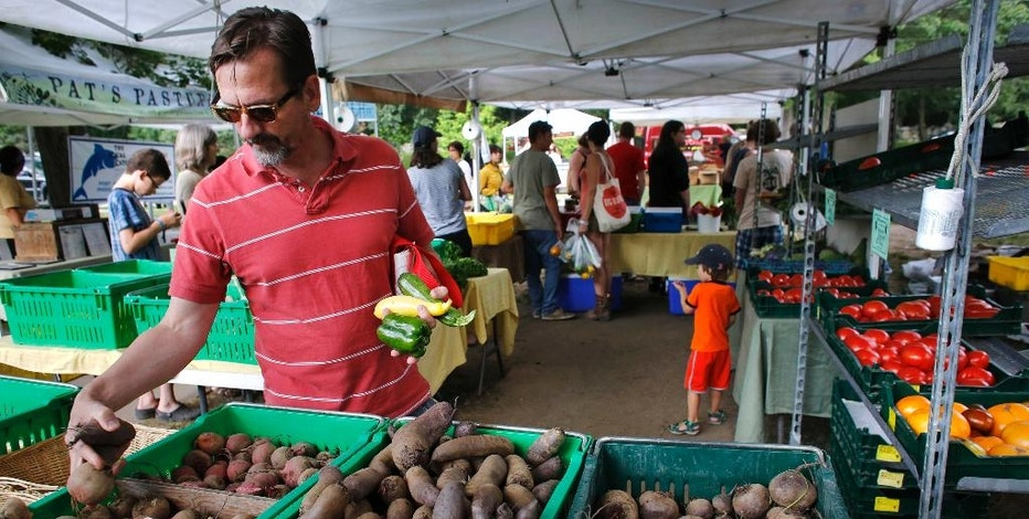 FILE - In this July 30, 2014 photo, David Mann, of Pawtucket, R.I., shops for vegetables at the Wishing Stone Farm stand at a farmers market, in Providence, R.I. The Commerce Department reports on wholesale stockpiles and sales in August on Thursday, Oct. 9, 2014. (AP Photo/Steven Senne, File)