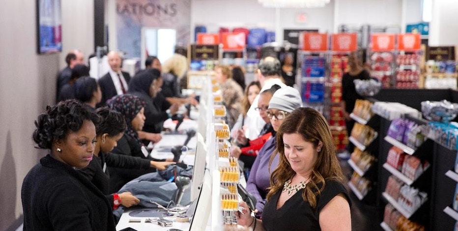 In this Oct. 28, 2014 photo, customers check out at the new Century 21 Department Store in Philadelphia. The Federal Reserve release its September report on consumer borrowing on Friday, Nov. 7, 2014. (AP Photo/Matt Rourke)