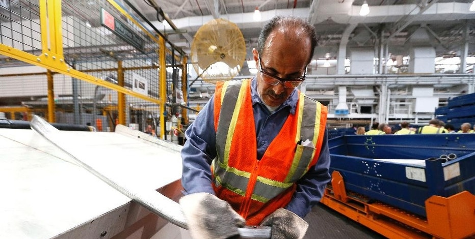 In this Nov. 11, 2014 photo, Agil Alhaddi inspects a roof rail for the 2015 Ford F-150 at the Dearborn Truck Plant in Dearborn, Mich. The Federal Reserve releases industrial production figures for October on Monday, Nov. 17, 2014. (AP Photo/Paul Sancya)
