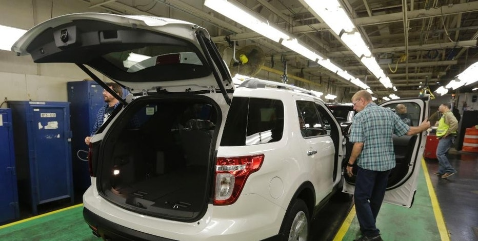 In this Oct. 22, 2014, photo, workers perform final inspections on 2015 Ford Explorers on the assembly line at the Chicago Ford Assembly Plant in Chicago. The Labor Department reports on U.S. producer price inflation in December on Thursday, Jan. 15, 2015. (AP Photo/M. Spencer Green)