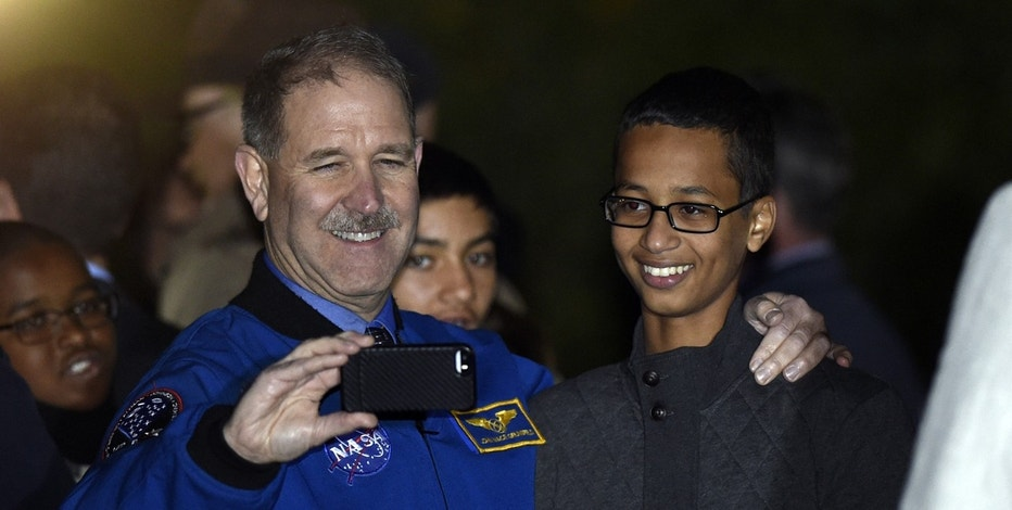 John M. Grunsfeld, left, NASA's Associate Administrator for the Science Mission Directorate, takes a photo with Ahmed Mohamed, right, the Texas teenager arrested after a homemade clock he brought to school was mistaken for a bomb during the second-ever White House Astronomy Night on the South Lawn of the White House in Washington, Monday, Oct. 19, 2015.