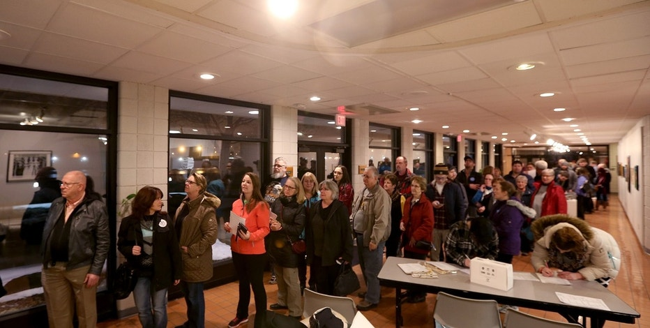 A line of people stretch down the hall at the Waterloo Center for the Arts during a caucus in Waterloo, Iowa, Monday, Feb. 1, 2016. (Brandon Pollock/The Courier via AP) MANDATORY CREDIT