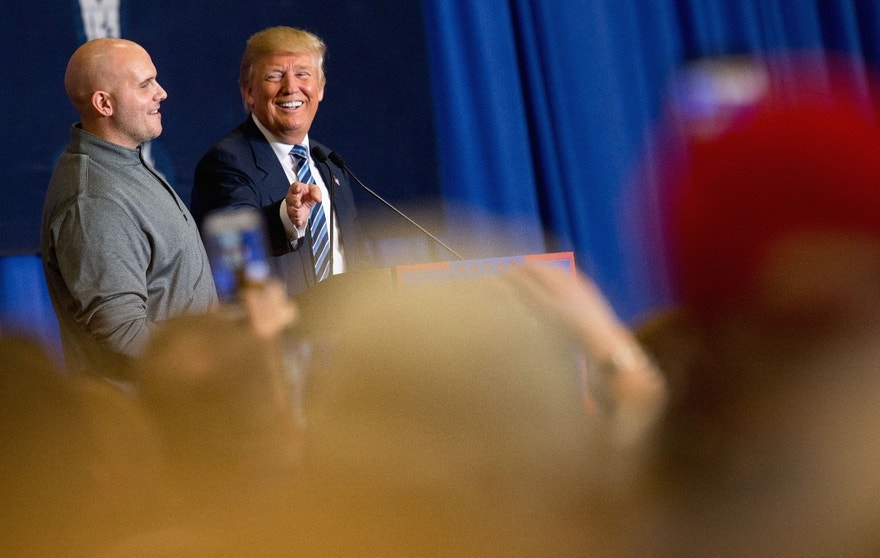 Republican presidential candidate Donald Trump invites a man from the audience up on stage to thank him after he interfered with a protester in the audience during a rally at the Riverview Park Activity Center in North Augusta, S.C., Tuesday, Feb. 16, 2016. (AP Photo/Andrew Harnik)