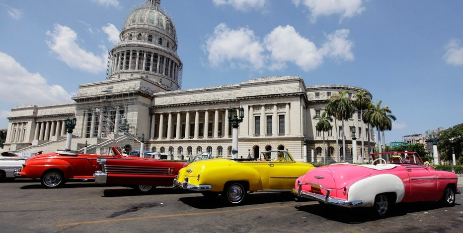 U.S.-made vintage convertible cars are parked beside the Capitol Building in Havana May 15, 2013.