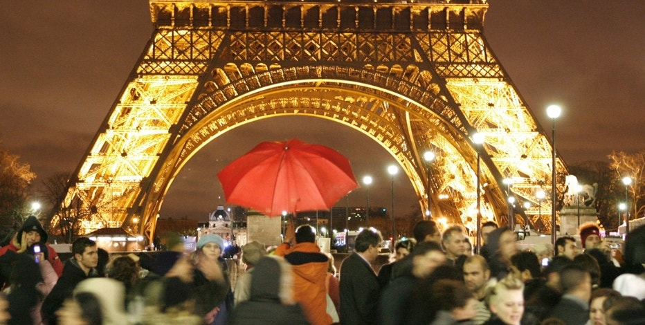Spectators gather in front of the Eiffel tower during New Year's eve celebrations January 1, 2007. Policemen blocked the access to the Eiffel Tower from Trocadero square to prevent last year's riots.   REUTERS/Charles Platiau (FRANCE)