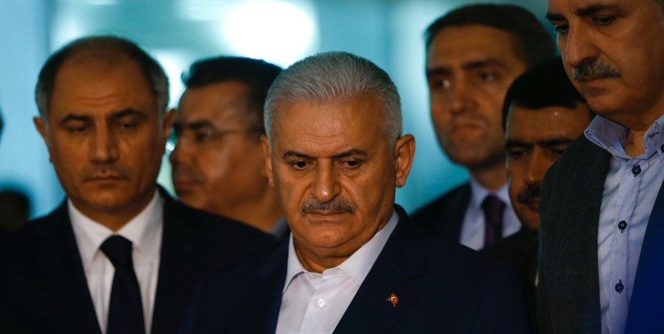 Turkey's Prime Minister Binali Yildirim (C) speaks to the press next to the Interior Miinister Efkan Ala (L) at the Ataturk airport in Istanbul, Turkey, following a multiple suicide bombing, June 29, 2016.  . REUTERS/Murad Sezer - RTX2IRYS