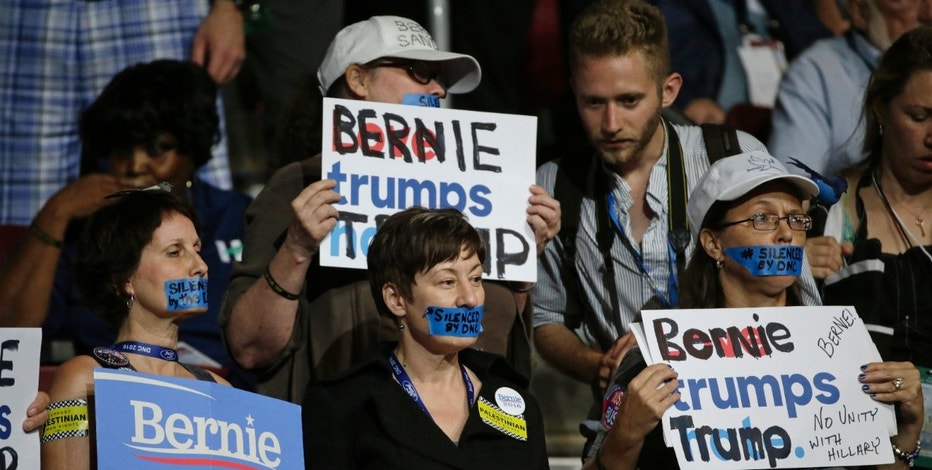Bernie Sanders supporters stand with tape over their mouths at the Democratic National Convention in Philadelphia, Pennsylvania, U.S. July 25, 2016. REUTERS/Gary Cameron - RTSJLV1