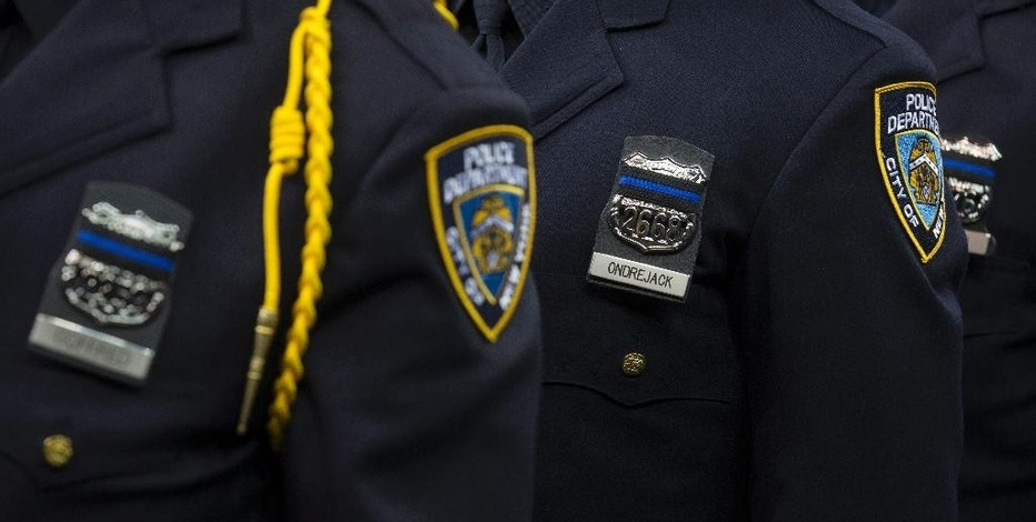 "FILE- In this Dec. 29, 2014, file photo, new recruits wear bands over their badges in honor of deceased officers Rafael Ramos and Wenjian Liu during a New York Police Academy graduation ceremony at Madison Square Garden in New York. The NYPD is sending its top brass to an in-house ""Twitter school"" as part of an effort to soften the NYPD's image and engage with the people they serve. Now, every precinct and some special commands have an account. (AP Photo/John Minchillo, File)"