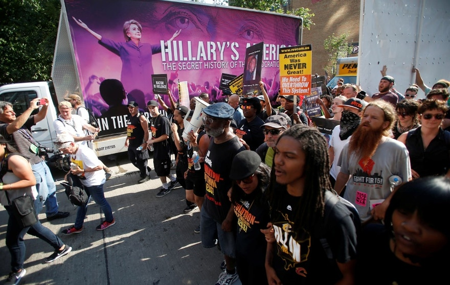 Protestors against police violence make their through the city pass an advertisement for a film featuring an image of Democratic Presidential Hillary Clinton near the Republican National Convention in Cleveland, Ohio, U.S., July 19, 2016.  REUTERS/Jim Urquhart - RTSIRVQ