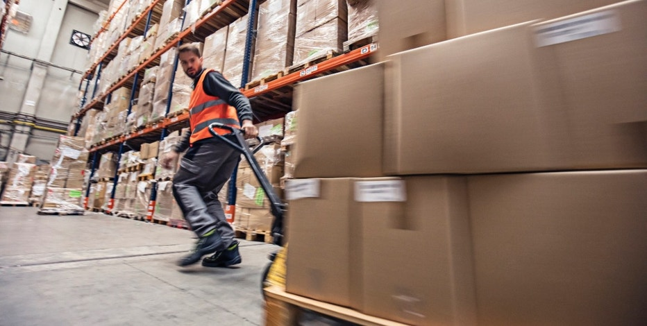 Motion blur of a man moving boxes in a warehouse.