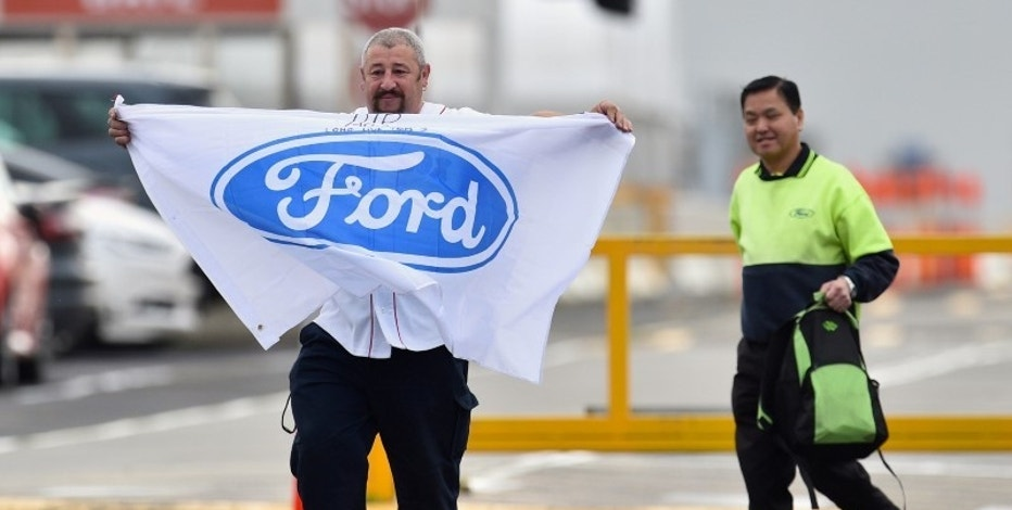 Nick Doria, a worker at the Ford Motor company's Broadmeadows Assembly Plant, holds a flag as he leaves the factory with a fellow worker before it closes in the Melbourne suburb of Campbellfield, Australia, October 7, 2016.     AAP/Julian Smith/via REUTERS