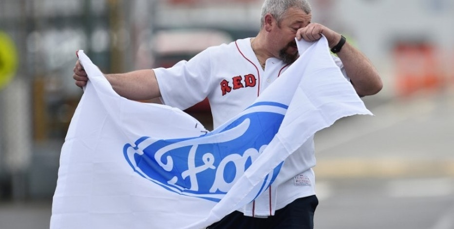 Nick Doria, a worker at the Ford Motor company's Broadmeadows Assembly Plant, wipes his eyes as he holds a flag and leaves the factory before it closes in the Melbourne suburb of Campbellfield, Australia, October 7, 2016.     AAP/Julian Smith/via REUTERS