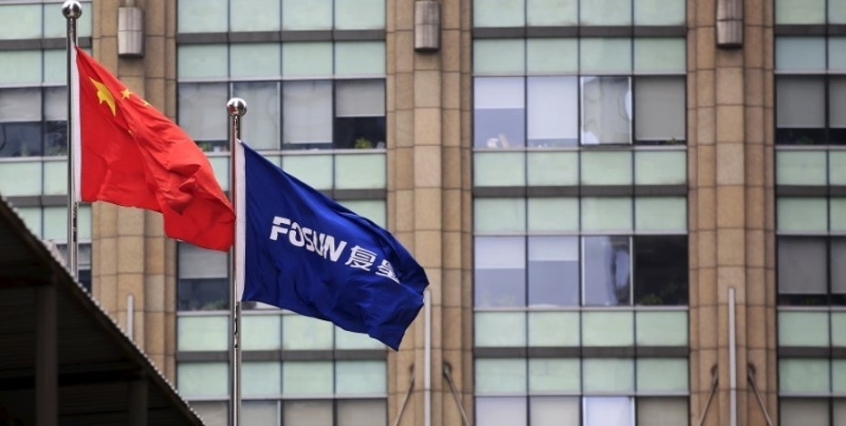 A Chinese national flag (L) flies in front of a building of the headquarters of Fosun International, in Shanghai, China, March 29, 2016. REUTERS/Aly Song