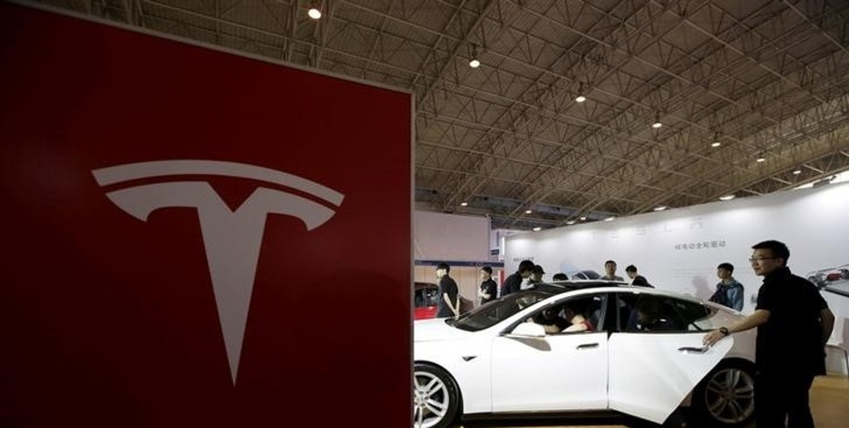 People view a Tesla car during the Auto China 2016 in Beijing, China, April 25, 2016. REUTERS/Jason Lee/File Photo
