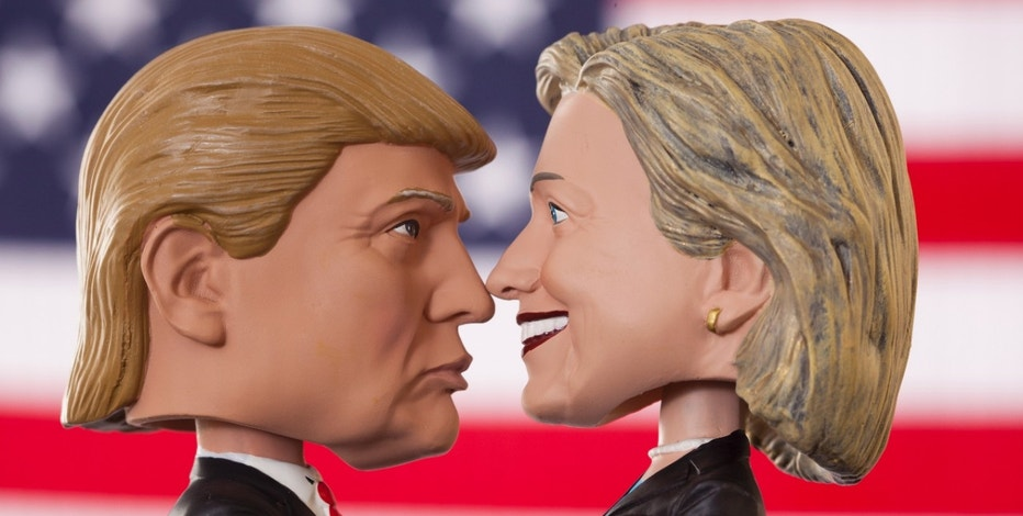 Lexington, KY, United States - October 5, 2016: Bobblehead dolls of 2016 presidential candidates Hillary Clinton and Donald Trump are pictured in front of an American flag.  Donald Trump and Hillary Clinton faced off as Republican and Democratic candidates during their 2016 bid for the title of President of the United States.  Produced by Royal Bobbles, these realistic figures have become popular preceding the November 8th election.