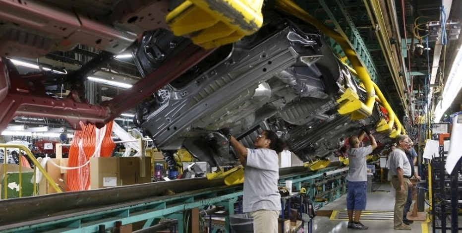 Assembly workers work on the underside of 2015 Ford Mustang vehicles on the production line at the Ford Motor Flat Rock Assembly Plant in Flat Rock, Michigan, August 20, 2015.  REUTERS/Rebecca Cook