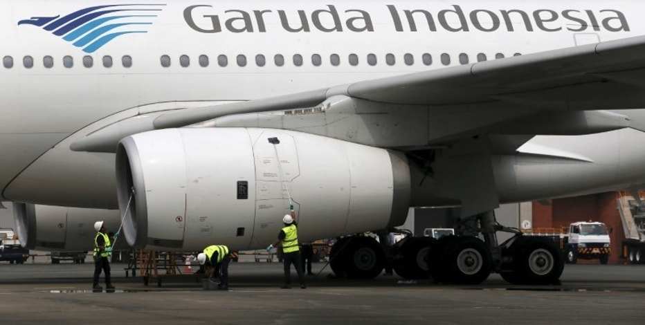 FILE PHOTO Workers clean the body of a Garuda Indonesia Airbus A320 aircraft inside Hangar 4 of PT Garuda Maintenance Facility (GMF) Aero Asia at Soekarno-Hatta airport in Jakarta, September 28, 2015. REUTERS/Beawiharta/File photo - RTSW94I