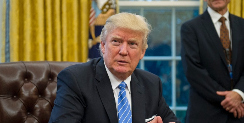 "United States President Donald Trump prepares to sign three Executive Orders in the Oval Office of the White House in Washington, DC on Monday, January 23, 2017. These concerned the withdrawal of the United States from the Trans-Pacific Partnership (TPP), a US Government hiring freeze for all departments but the military, and ""Mexico City"" which bans federal funding of abortions overseas. Credit: Ron Sachs / Pool via CNP - NO WIRE SERVICE- Photo by: Ron Sachs/picture-alliance/dpa/AP Images"