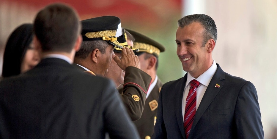In this Wednesday, Feb. 1, 2017 photo, Venezuela's Vice-President Tareck El Aissami, right, is saluted by Boilivarian Army officer upon his arrival for a military parade at Fort Tiuna in Caracas, Venezuela. A bipartisan group of 34 U.S. lawmakers has sent a letter to President Donald Trump urging him to step up pressure on Venezuela's government by immediately sanctioning officials responsible for corruption and human rights abuses. The letter, partly prompted by an Associated Press investigation on graft in Venezuela's food imports, also calls for a thorough probe into alleged drug trafficking and support for Middle Eastern terror groups by the country's vice president. (AP Photo/Fernando Llano)
