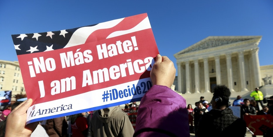 A protester holds her sign up as immigrants and community leaders rally in front of the U.S. Supreme Court to mark the one-year anniversary of President Barack Obama's executive orders on immigration in Washington, November 20, 2015.