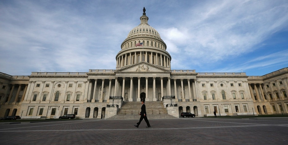 A lone worker passes by the U.S. Capitol Building in Washington, October 8, 2013. A few faint glimmers of hope surfaced in the U.S. fiscal standoff, both in Congress and at the White House, with President Barack Obama saying he would accept a short-term increase in the nation's borrowing authority to avoid a default. REUTERS/Jason Reed   (UNITED STATES - Tags: POLITICS) - RTX143RN