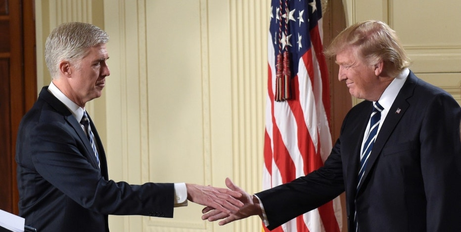10th U.S. Circuit Court of Appeals Judge Neil Gorsuch reaches to shake hands with President Donald Trump after his announcement as President Trump's choice for Supreme Court Justice during a televised address from the East Room of the White House in Washington, Tuesday, Jan. 31, 2017. (AP Photo/Susan Walsh)