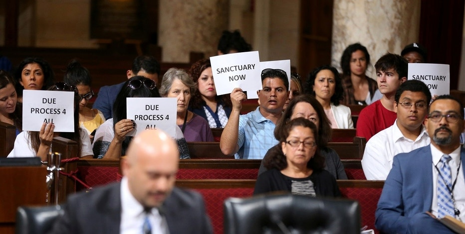 Immigrant supporters protest duirng the Los Angeles City Council ad hoc committee on immigration meeting to discuss the city's response to threats by the Trump administration to cut funding from Los Angeles and other jurisdictions which federal officials say are providing sanctuary to illegal immigrants arrested for crimes, in Los Angeles, California, U.S., March 30, 2017. REUTERS/Lucy Nicholson - RTX33FY5