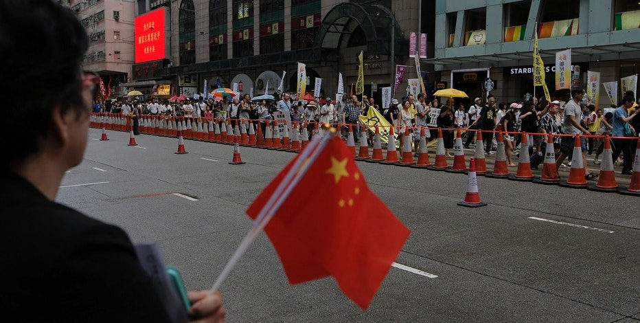 A woman holding a China national flag as protesters march during the annual pro-democracy protest in Hong Kong, Saturday, July 1, 2017 to mark the the 20th anniversary of handover to China. Thousands joined an annual protest march in Hong Kong, hours after Chinese President Xi Jinping wrapped up his visit to the city by warning against challenges to Beijing's sovereignty. (AP Photo/Kin Cheung)