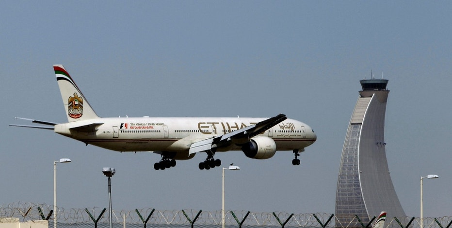 FILE - In this May 4, 2014 file photo, an Etihad Airways plane prepares to land at the Abu Dhabi airport in the United Arab Emirates. The capital of the United Arab Emirates became the first city to find itself exempt from a U.S. ban on laptop computers being in airplane cabins, the country's flag carrier said Sunday. (AP Photo/Kamran Jebreili, File)