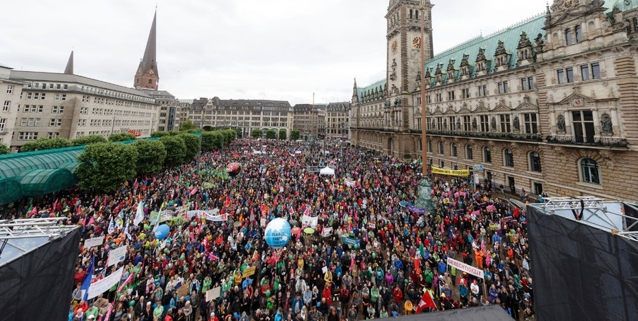 Participants of the demonstration 'G20 Protest Wave' gather in front of the city hall in Hamburg, Germany, Sunday, July 2, 2017 to protest againt the upcoming G20 summit on July 7 and July 8, 2017.  (Markus Scholz/dpa via AP)