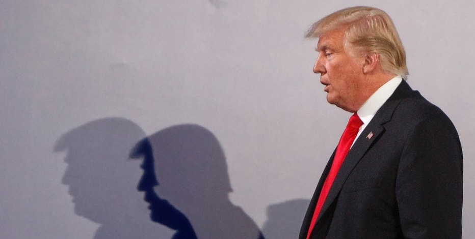 U.S. President Donald Trump casts shadows on the wall as he walks with Poland's President Andrzej Duda at the end of a joint press conference, in Warsaw, Poland, Thursday, July 6, 2017.(AP Photo/Czarek Sokolowski)
