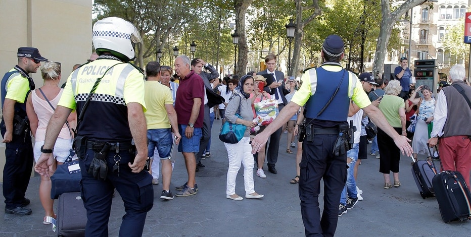 Police officers tell members of the public to leave the scene in a street in Barcelona, Spain, Thursday, Aug. 17, 2017. Police in the northern Spanish city of Barcelona say a white van has jumped the sidewalk in the city's historic Las Ramblas district, injuring several people.
