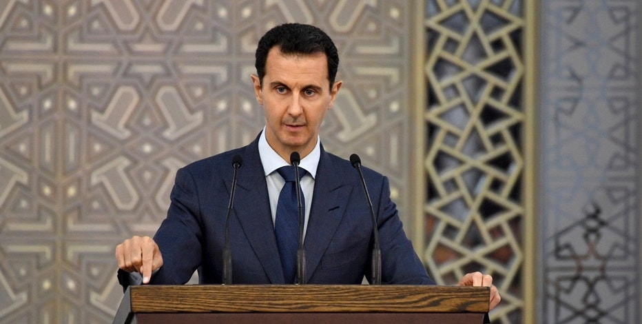 In this photo released by the official Facebook page of the Syrian Presidency, Syrian President Bashar Assad speaks to Syrian diplomats, in Damascus, Syria, Sunday, Aug. 20, 2017. In defiant comments Sunday, Assad blasted the West, rejecting any security cooperation or reopening of embassies in Damascus before those countries cut relations with opposition groups. In the speech, Assad praised Russia, Iran, China and Lebanon's Hezbollah for supporting his government. (Syrian Presidency Facebook page via AP)