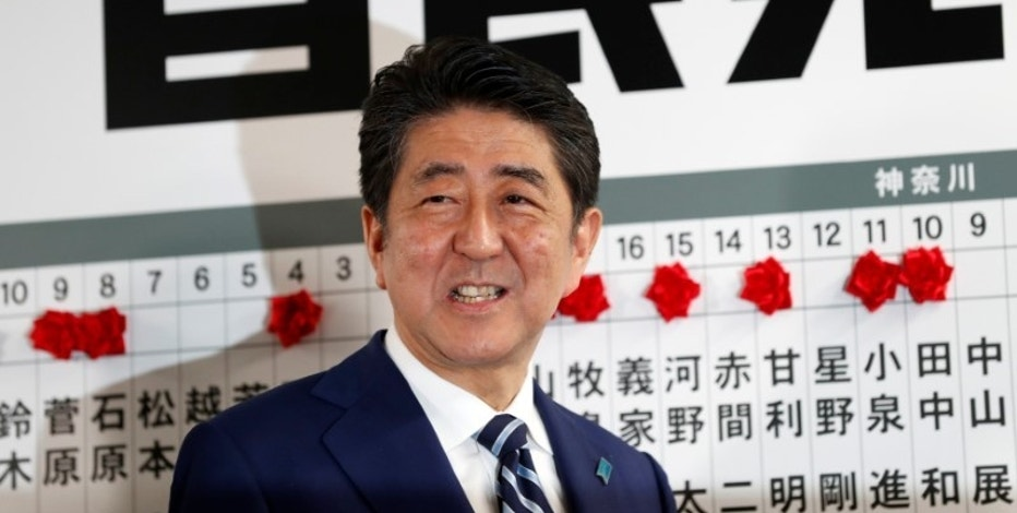 Japan's Prime Minister Shinzo Abe, leader of the Liberal Democratic Party (LDP), smiles as he puts a rosette on the name of a candidate who is expected to win the lower house election, at the LDP headquarters in Tokyo, Japan October 22, 2017. REUTERS/Kim Kyung-Hoon
