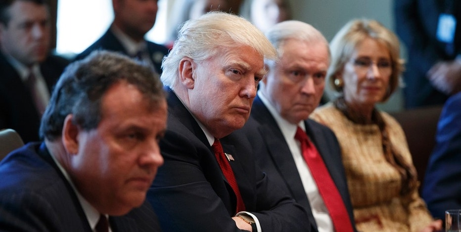 President Donald Trump listens during an opioid and drug abuse listening session, Wednesday, March 29, 2017, in the Cabinet Room of the White House in Washington. From left, New Jersey Gov. Chris Christie, Trump, Attorney General Jeff Sessions, and Education Secretary Betsy DeVos. (AP Photo/Evan Vucci)