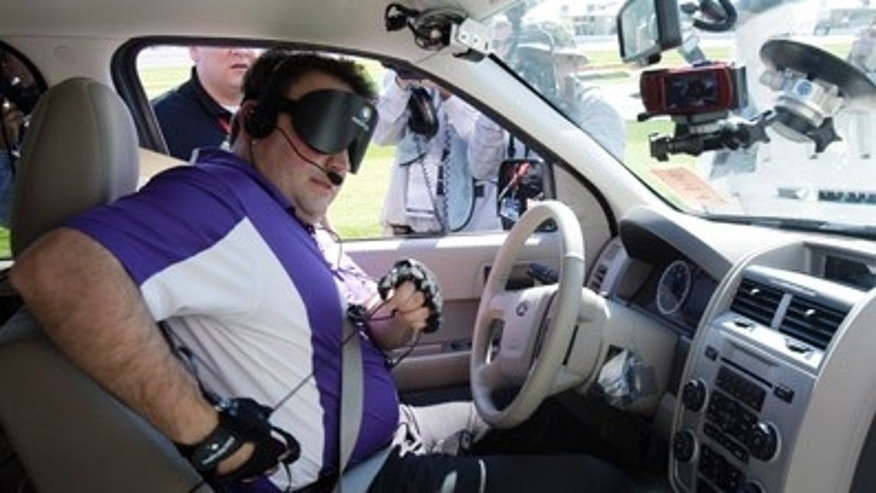 Blind driver Mark Riccobono makes adjustments to his equipment before driving a specially equipped car around the road course at Daytona International Speedway in Daytona Beach, Fla., Saturday, Jan. 29, 2011. (AP Photo/John Raoux)