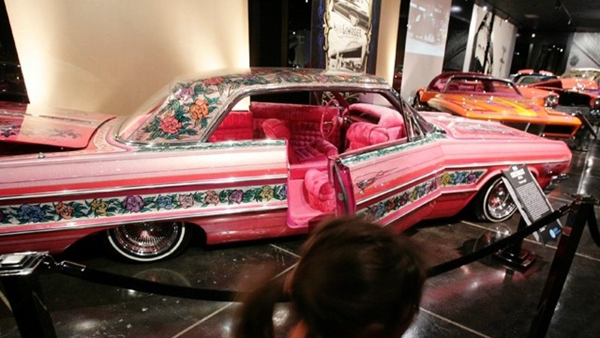 "FILE - In this Feb. 10, 2008 file photo, visitors to the Peterson Automobile Museum examine a 1964 Chevrolet Impala ""Gypsy Rose"" lowrider in Los Angeles. She was a cover girl, had a bit part in a popular '70s TV show and was an icon of car culture. ""Gypsy Rose,"" an award-winning Chevy Impala admired for its elaborate floral paint job, was known in the world of cruising low-riders as one of the most flamboyantly tricked-out muscle cars of a generation. On Saturday, the rose-covered ride will lead a funeral procession through East L.A., behind the hearse that carries its owner to his final resting place. (AP Photos/Ric Francis, File)"