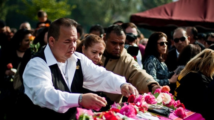 "Javier Valadez Jr. places roses on his Uncle Jesse Valadez's casket at the Rose Hills Memorial Park in Whittier, Calif. Valadez was a longtime member of the Imperial Car Club and owner of the lowrider ""Gypsy Rose"". (AP Photo/ Bret Hartman)"