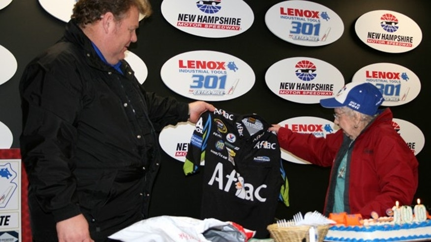 Vice President and General Manager Jerry Gappen hands Rachel Gilbert a jacket signed by NASCAR driver Carl Edwards