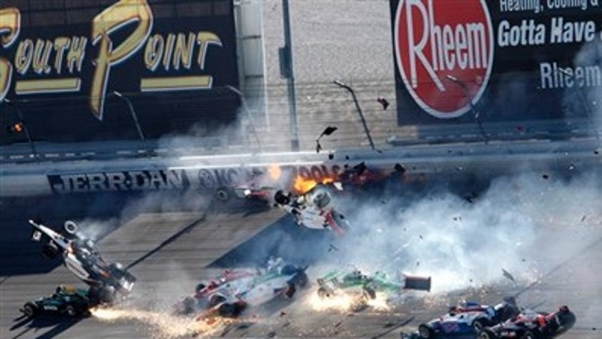 Drivers, including Dan Wheldon (77, in air at left), crash during a wreck that involved 15 cars during the IndyCar Series' auto race at Las Vegas Motor Speedway in Las Vegas.