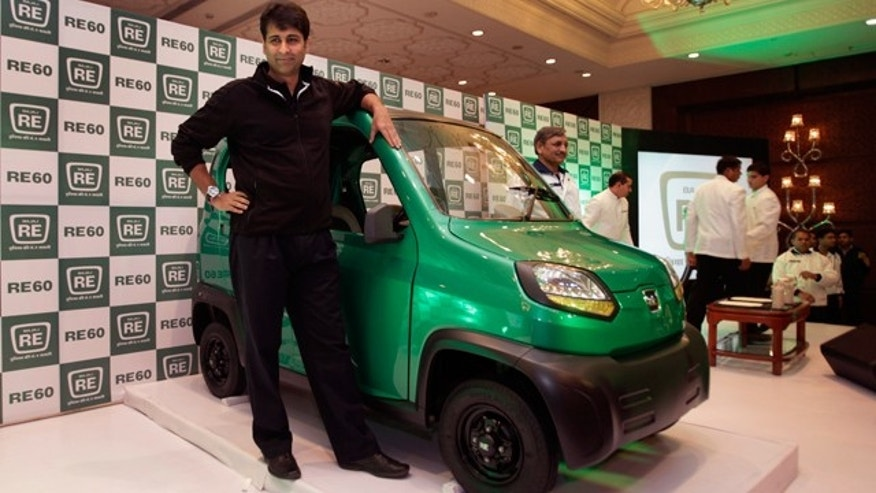 Bajaj Auto Managing Director Rajiv Bajaj stands next to the RE60